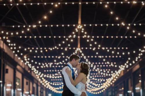 bride and groom kissing under lights in beloit Wisconsin