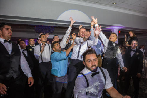 guys fighting for the brides garter at a reception