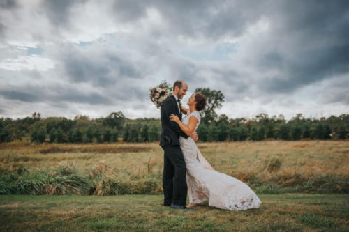 bride and groom hugging under cloudy skies at Orchard Ridge Farms the Pavilion in Rockton Illinois
