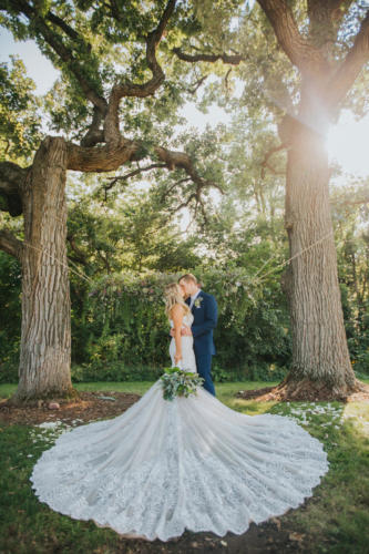 bride and groom kissing under oak trees at Orchard Ridge Farms the Pavilion in Rockton Illinois