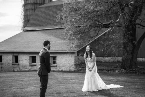 bride laughing at her groom with limestone barn in background