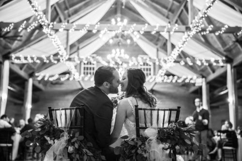 bride and groom kissing under cafe lights at their reception