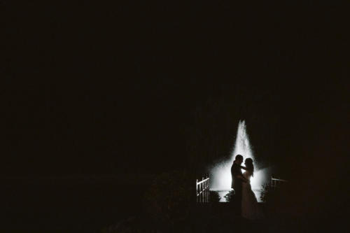 nigh time photograph of wedding couple by the fountain at Orchard Ridge Farms the Pavilion in Rockton Illinois