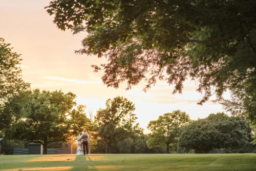 bride and groom walking into sunset at rockford country club