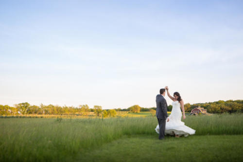 bride dancing and twirling dress in a field