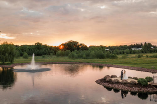 bride and groom at sunset by pond at Orchard Ridge Farms the Pavilion in Rockton Illinois
