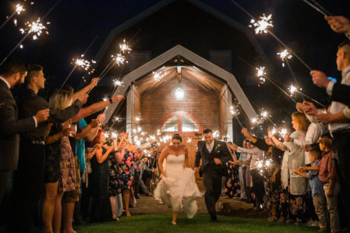 bride and groom running through sparklers at Orchard Ridge Farms the Pavilion in Rockton Illinois
