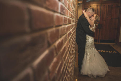 bride and groom kissing along brick wall